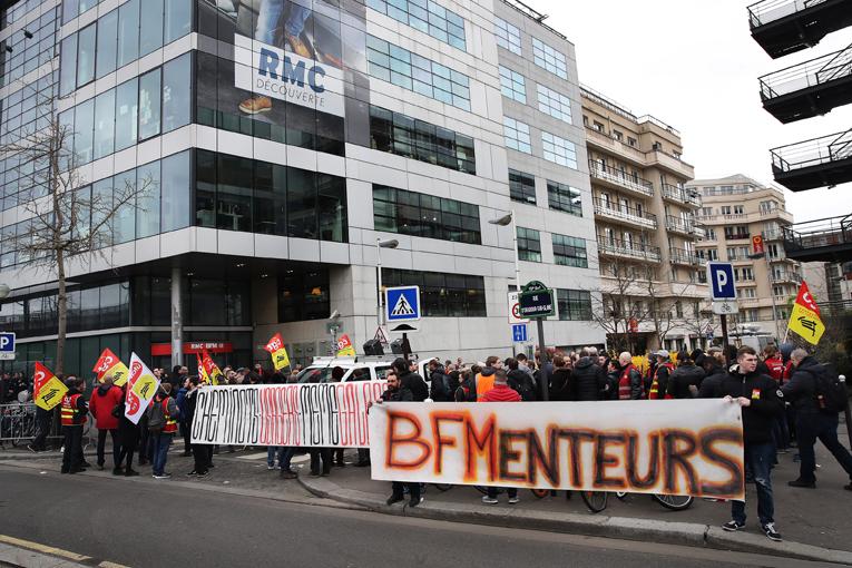 Manfestation  des cheminots CGT devant le siège de BFM TV, à l'occasion de la première journée de grève des cheminots d'avril 2018. Les manifestants entendaient dénoncer la désinformation de la chaine et de ses éditorialistes et reporters, ainsi que l'accès inégal aux médias entre défenseurs et détracteurs de la casse de la SNCF voulue par le gouvernement.